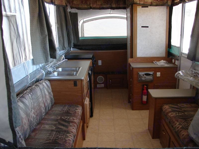 Kitchen includes microwave, three burner stove, oven, double sink, hot/cold water, refrigerator and freezer. Hard bathroom walls with toilet and shower with hot water, a perfect ending to a day outdoor..!. Fleetwood Highlander Sequoia