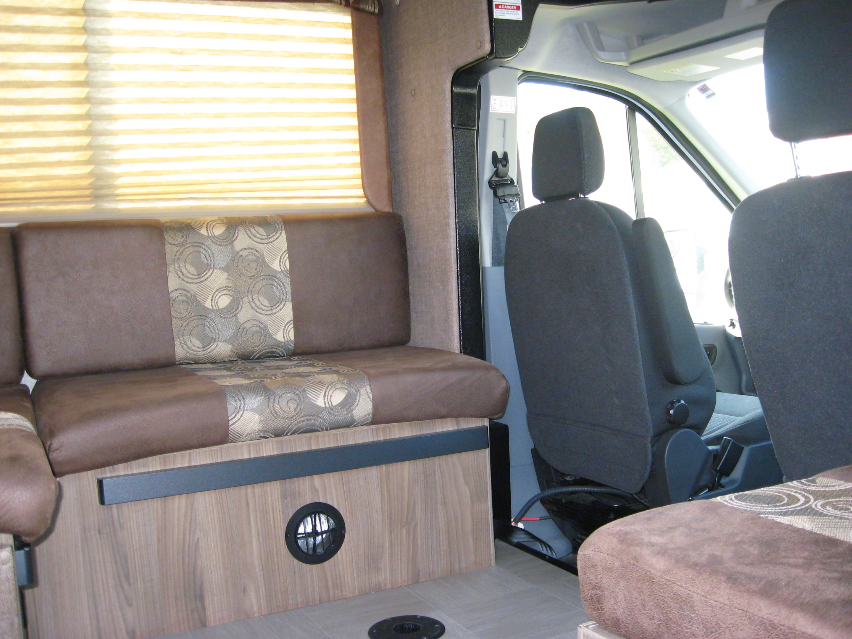 The dining area directly behind the driver's seat features a removable tabletop which allows the area to be converted into additional sleeping space.  A jump seat (shown in the lower right corner of this picture) gives additional seating at mealtimes.. Coachmen Freelander 2017