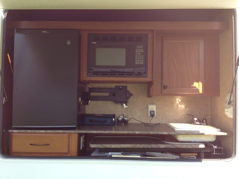 Outdoor kitchen with fridge, microwave, and sink.. Heartland Sundance 2011