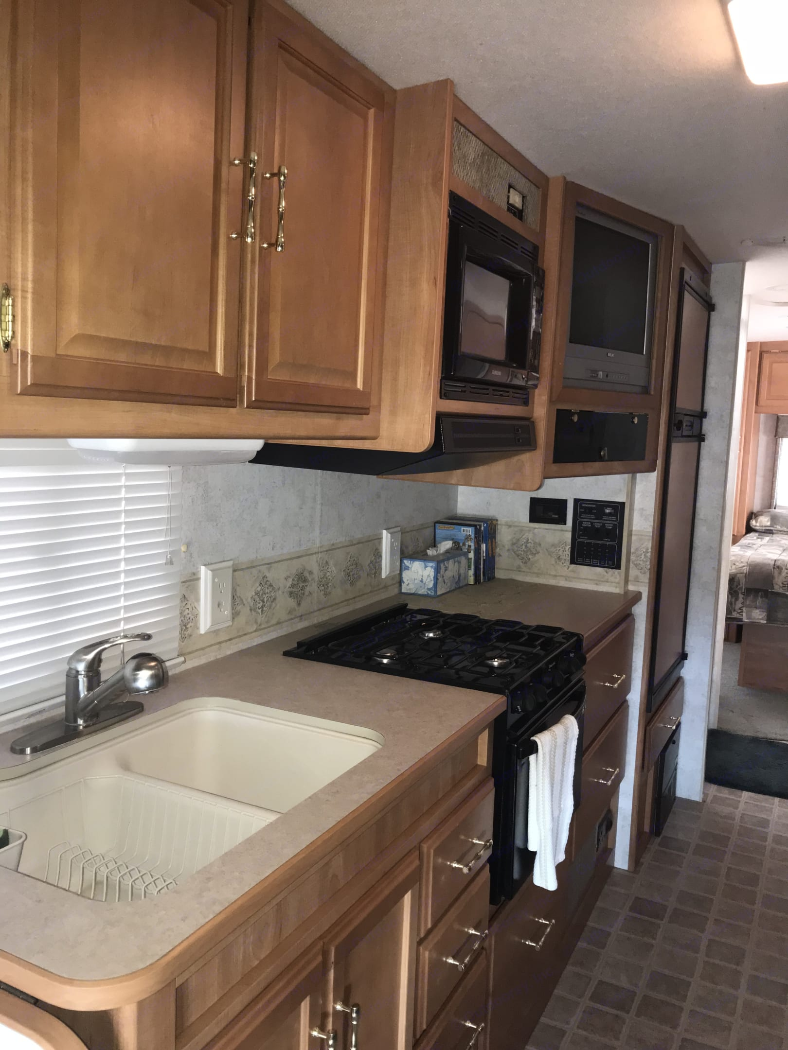 Kitchen area complete with microwave, stove top and oven.  Comes equipped with all cooking supplies.. Winnebago Minnie Winnie 2005