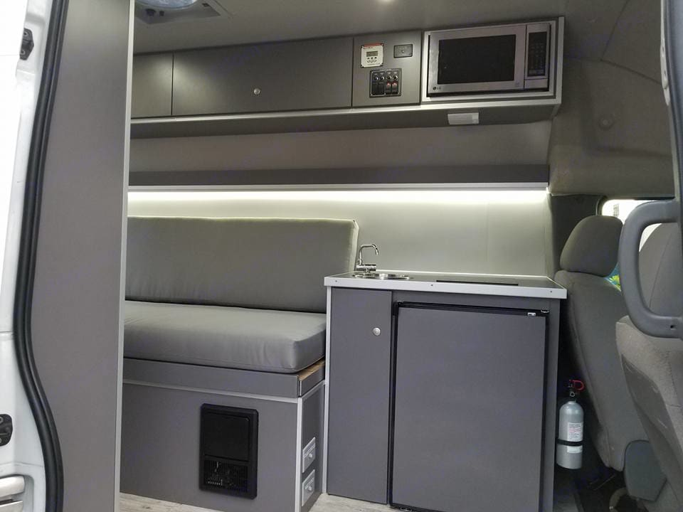 This shows the kitchen area with microwave on top, sink and induction cooktop, and fridge underneath with a freezer too.  Next to fridge is a cabinet with easy to empty gray water container.. Nissan NV2500 2012