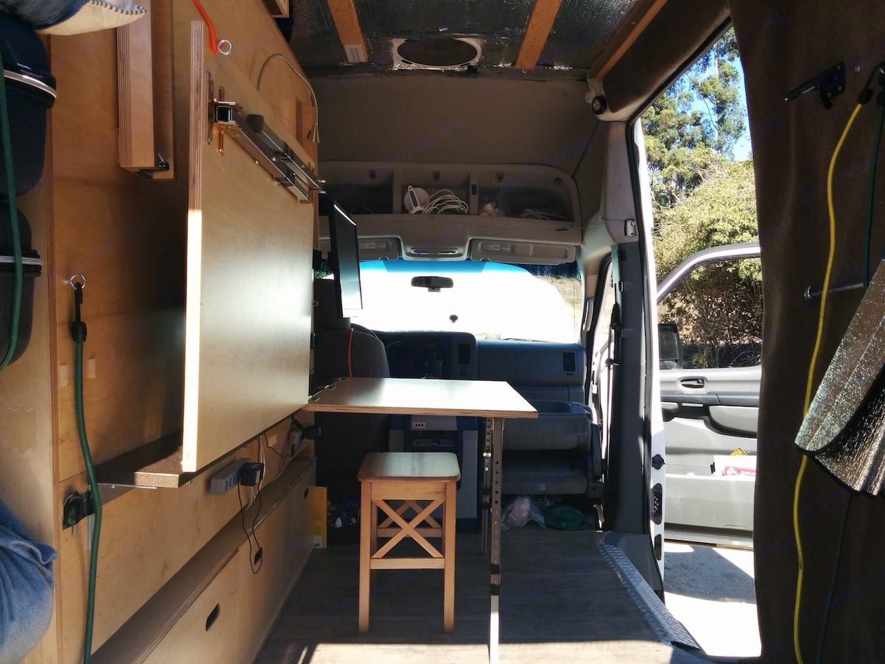 """Daytime setup.  Two desks + two 24"""" monitors.  Desks double as cooking/eating area.. Nissan NV2500 2012"""
