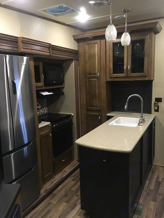 Wonderful kitchen with solid wood cabinets and stainless steel side by side residential fridge with double freezer underneath, double sink, gas oven and range top and microwave.. Coachmen Chaparral 2017