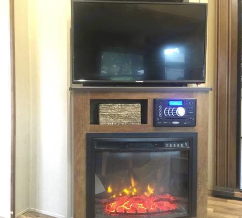 """40"""" TV with DVD and CD player and radio with options to send sound to 3 separate areas of the RV including this room, the bedroom, or outside. Also there are 2 additional smart TVs in the camper in the front and back bedrooms. The electric fireplace is adjustable and heats this room nicely and you can even adjust the flame brightness which can create a great ambiance.. Coachmen Chaparral 2017"""