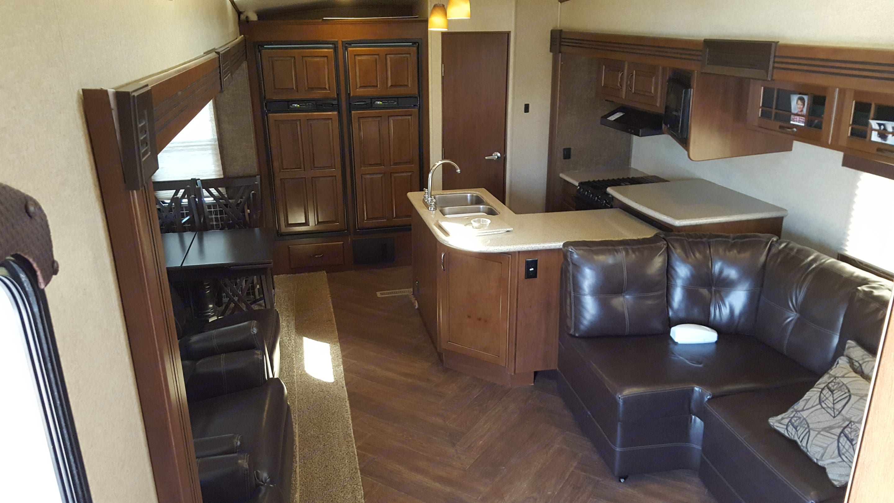 Kitchen in rear of living area. Dining table on left seats four.  Sectional chair stowed on left moves in front of island.. Heartland Sundance 2014