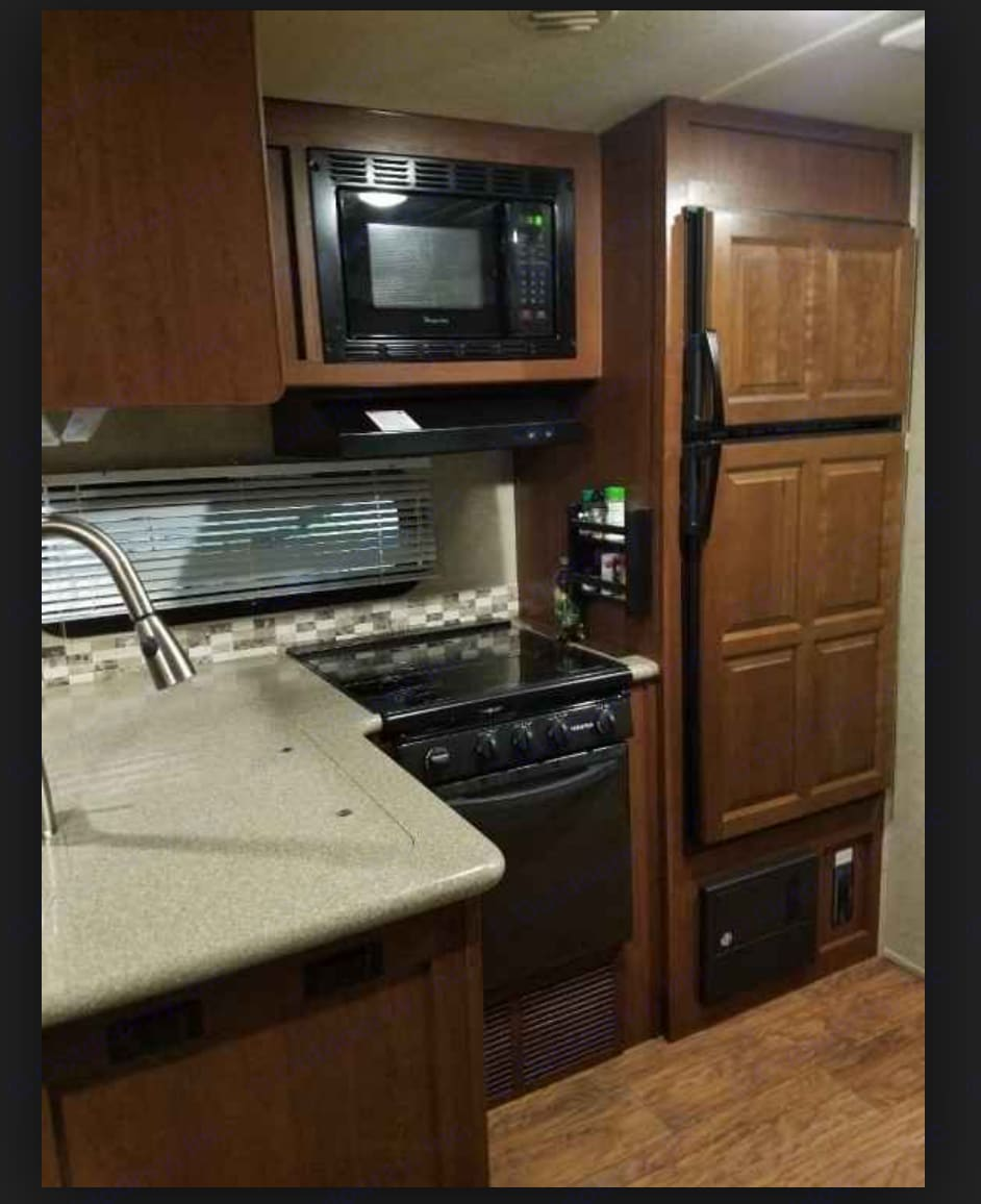 Interior kitchen. Double sink, stove and oven, refrigerator and freezer, microwave. Plenty of storage. . Forest River Rockwood Signature Ultra 2015