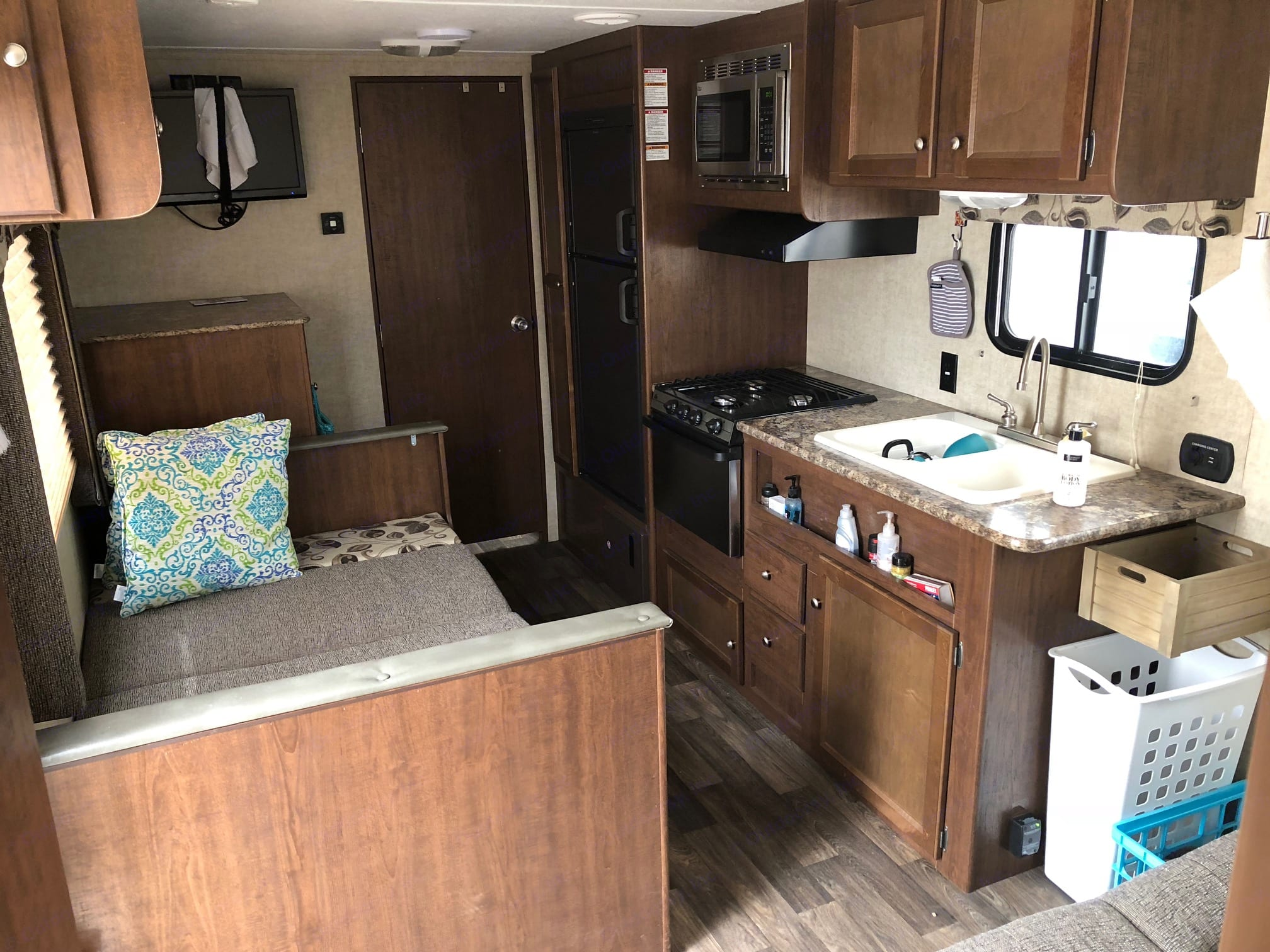 This is the main living area with the table folded down to show an additional bed.  Kitchen has a refrigerator, stove, oven and microwave.  . Keystone Hideout 2016