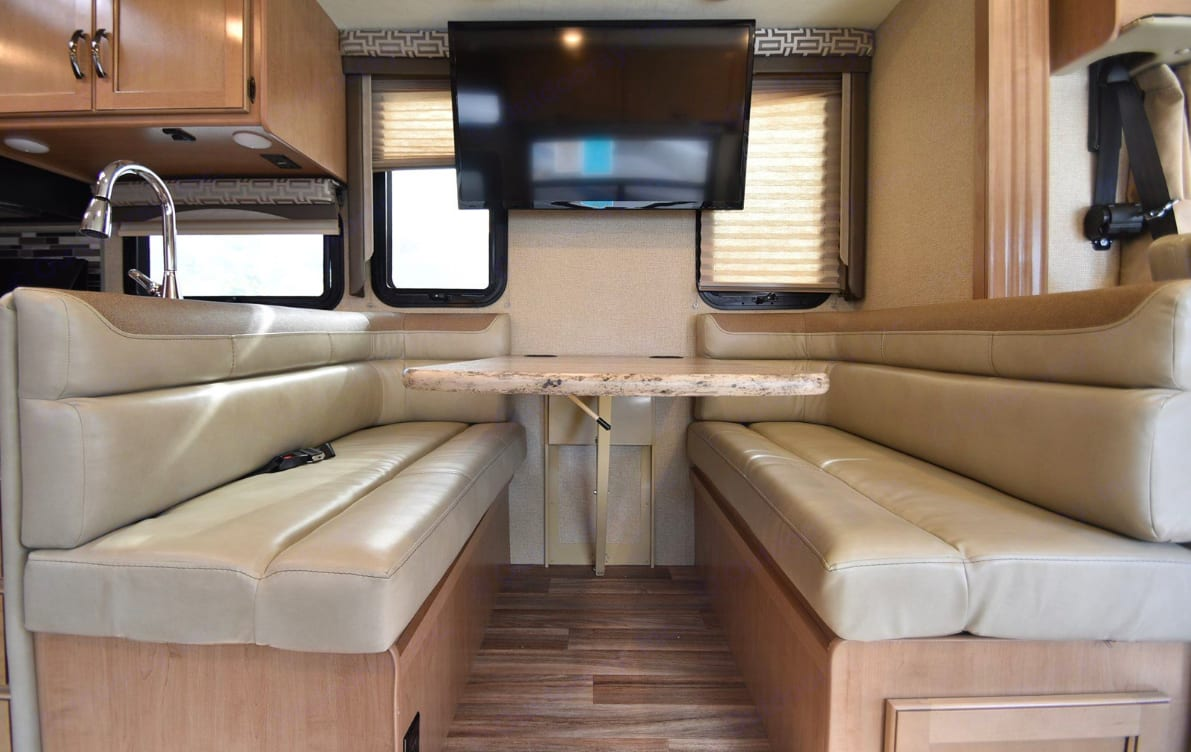 """Modern Leather Dinette with 40"""" TV. Dinette folds down into a bed.. Thor Motor Coach A.C.E 2018"""