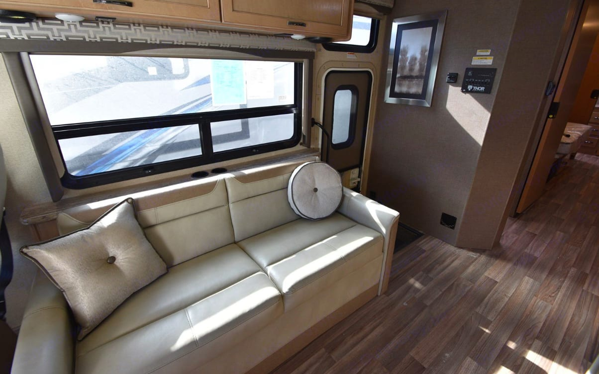 This sleek and comfortable leather sofa in the front living area also folds out into a bed.. Thor Motor Coach A.C.E 2018