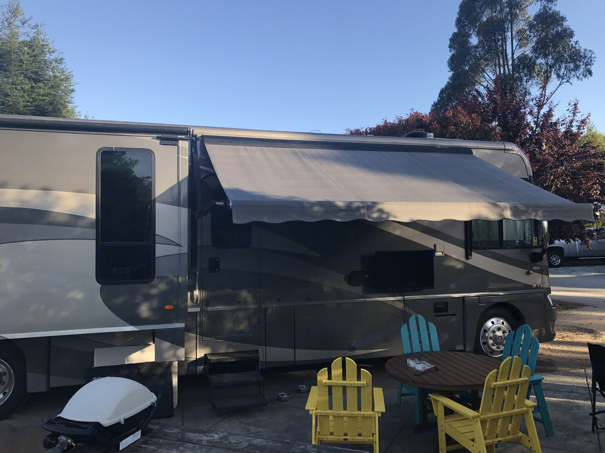 Opened up and hanging out. Awning features a wind sensor for peace of mind. Includes exterior TV setup with HD satellite dish. Also includes Webber grille and dual high output burners you can hook right up to the RV propane tank.. Winnebago Adventurer 2008