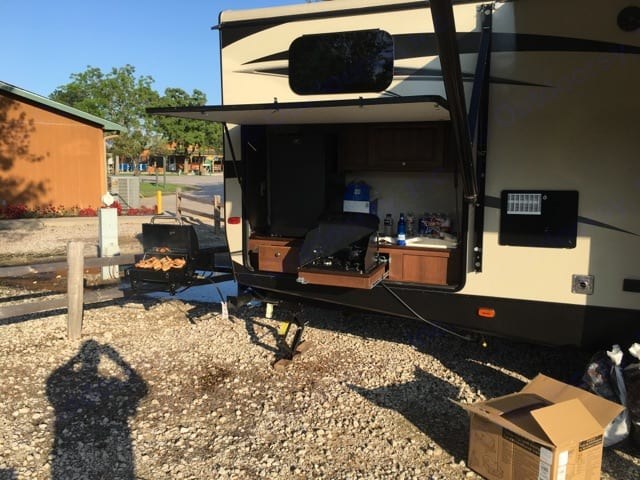 Outdoor kitchen with sink & refrigerator, storage and Kuerig.  Bunk window above outdoor kitchen.. Keystone Bullet Premier 2016