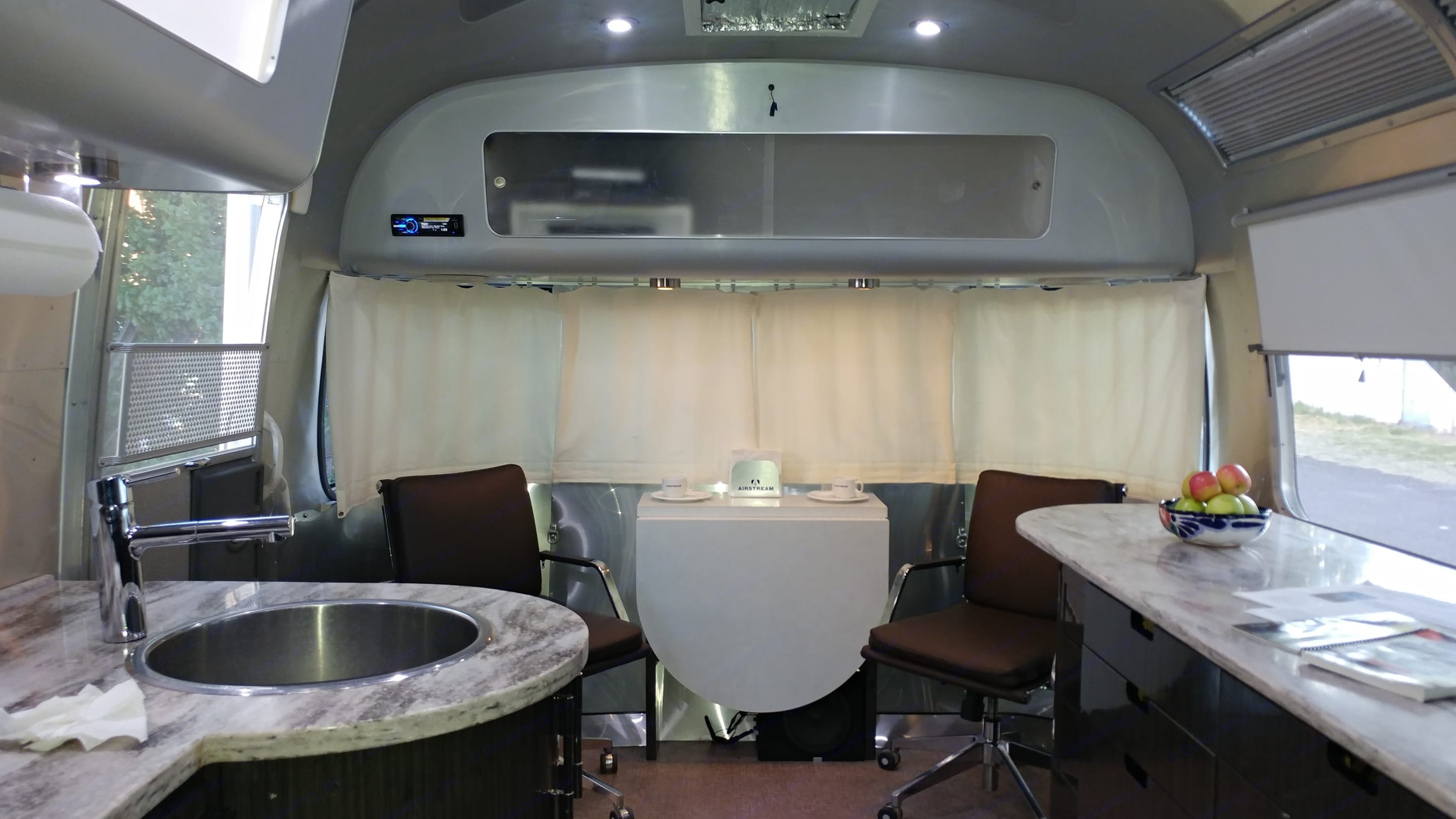 """The dining table easily folds creating a ballroom-like living area (for an Airstream). Watch TV and stretch you legs on the Italian leather foot stool.  The TV is upgraded to a 42"""" HD with provided DISH satellite...the autosearch small dome makes it easy to sync. Bluetooth cellphone sync with interior microphones for hands-free  talking. Or set your I-phone into the built-in  port and stream through the incredible sound system including a big sub-woofer. . Airstream International 2014"""