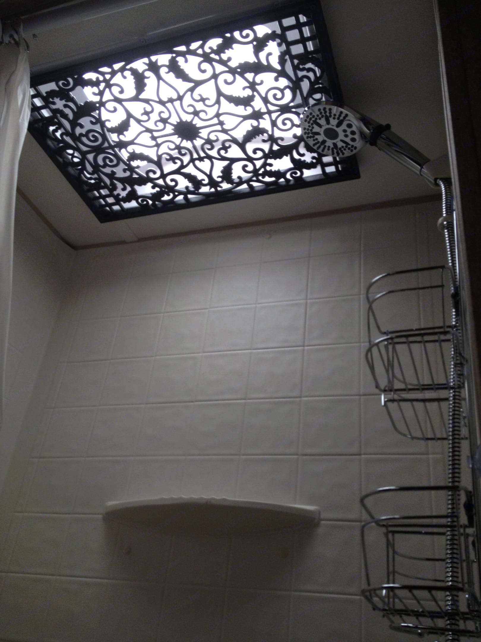 Decorated skylight and upgraded shower head inside shower/tub combo. Hanging shower organizer is no longer in the trailer. . Skyline Ecocamp 2014