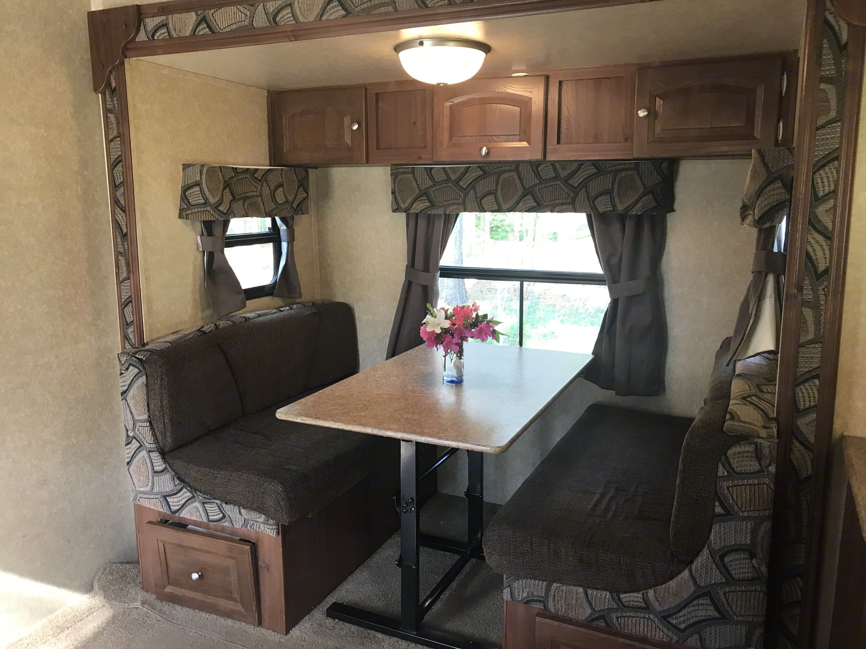 Dining area converts into bed for two. Storage below the bench seats. In addition, the dining area is a slideout that greatly increases the square footage inside the camper. A must-have feature!. Forest River Rockwood Roo 2011
