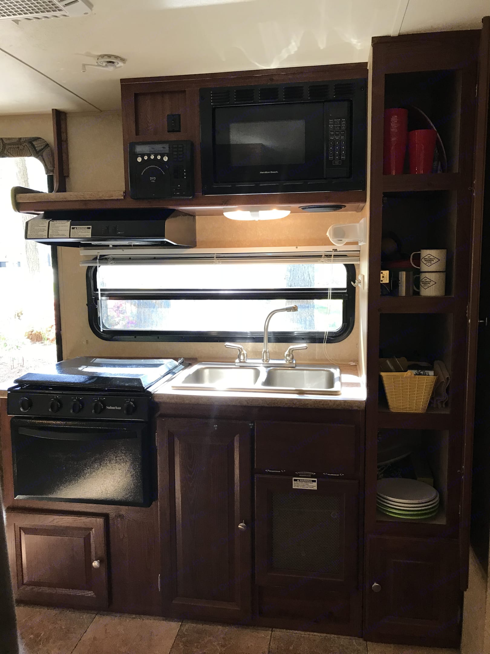 Kitchenette features microwave, Keurig coffee maker, gas range, oven, sink with hot water and abundant storage.. Forest River Rockwood Roo 2011