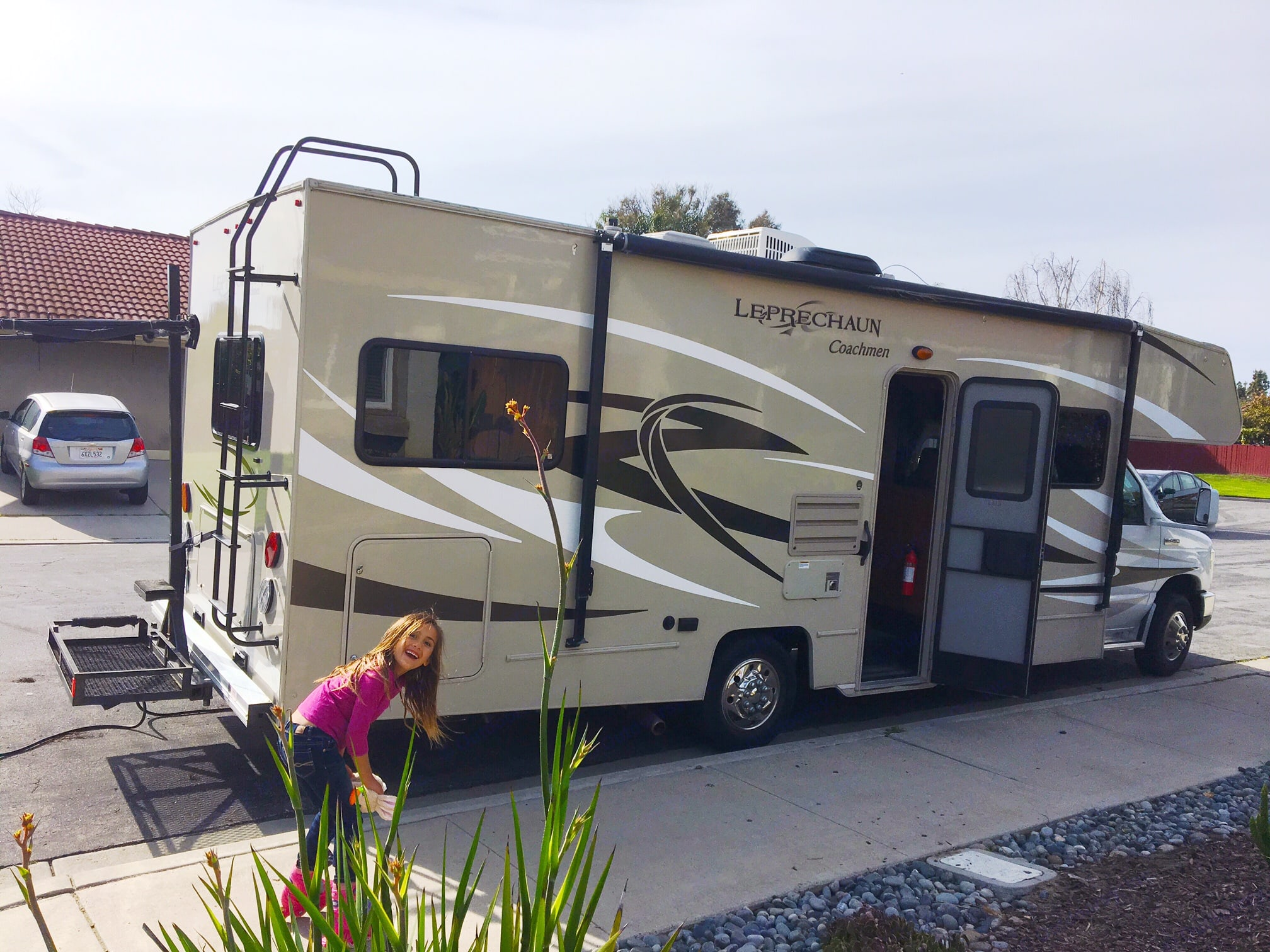 Exterior with vertical surfboard rack attached at hitch. Coachmen Leprechaun 2015