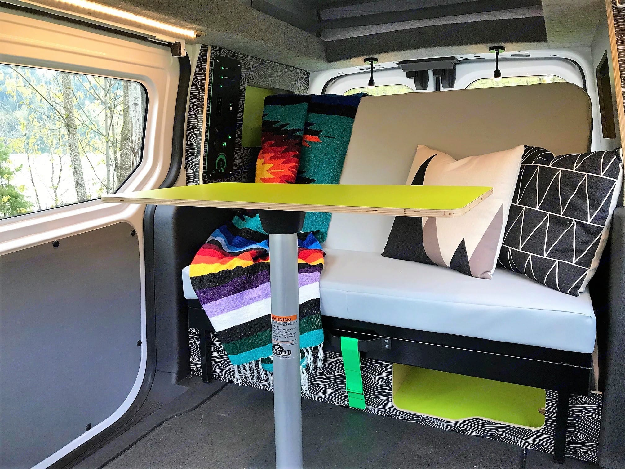 Inside, you'll find a couch and table for two.. Ford Transit Connect 2016