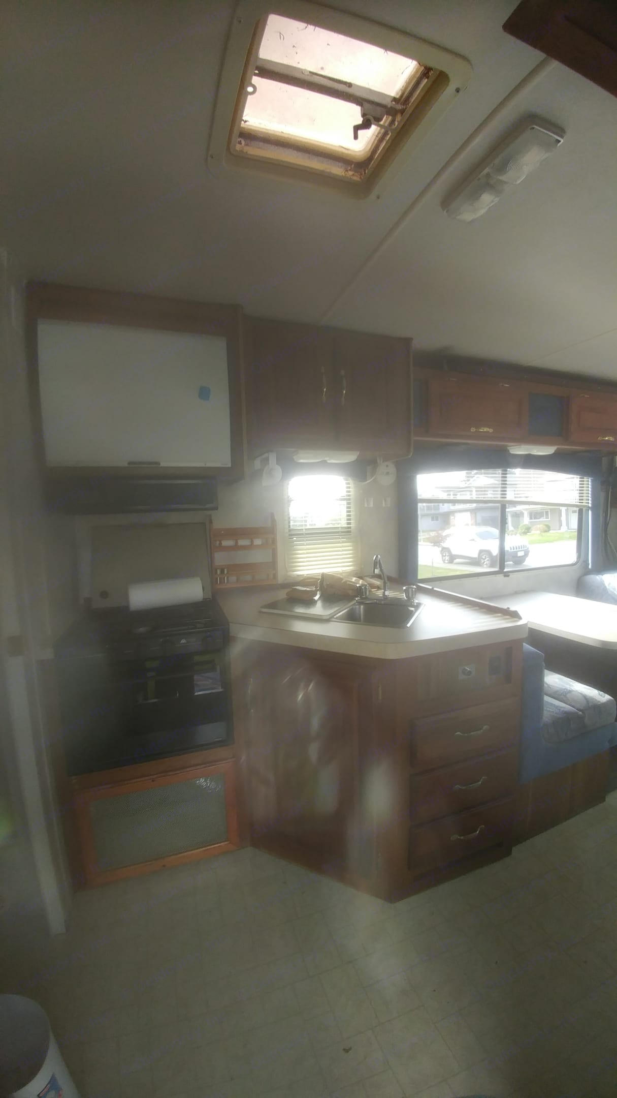 The kitchen has a four burners stove and an oven. Microwave was replaced with extra cupboard for storing food.. Thor Motor Coach Four Winds 1997