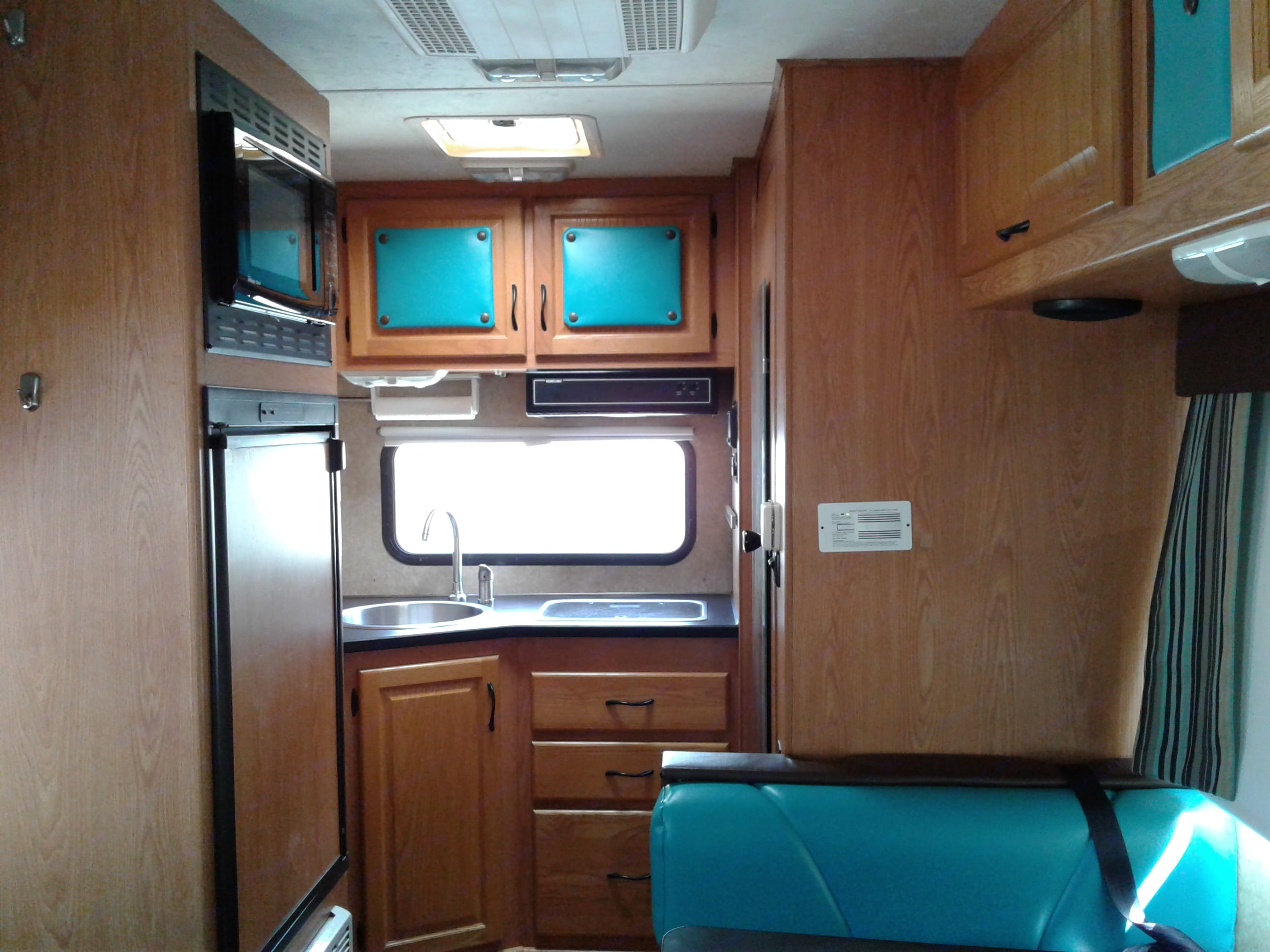 The kitchen has a 2 burner stove, and a sink. Cabinets above, and drawers under.. Thor Motor Coach Four Winds Majestic 2010