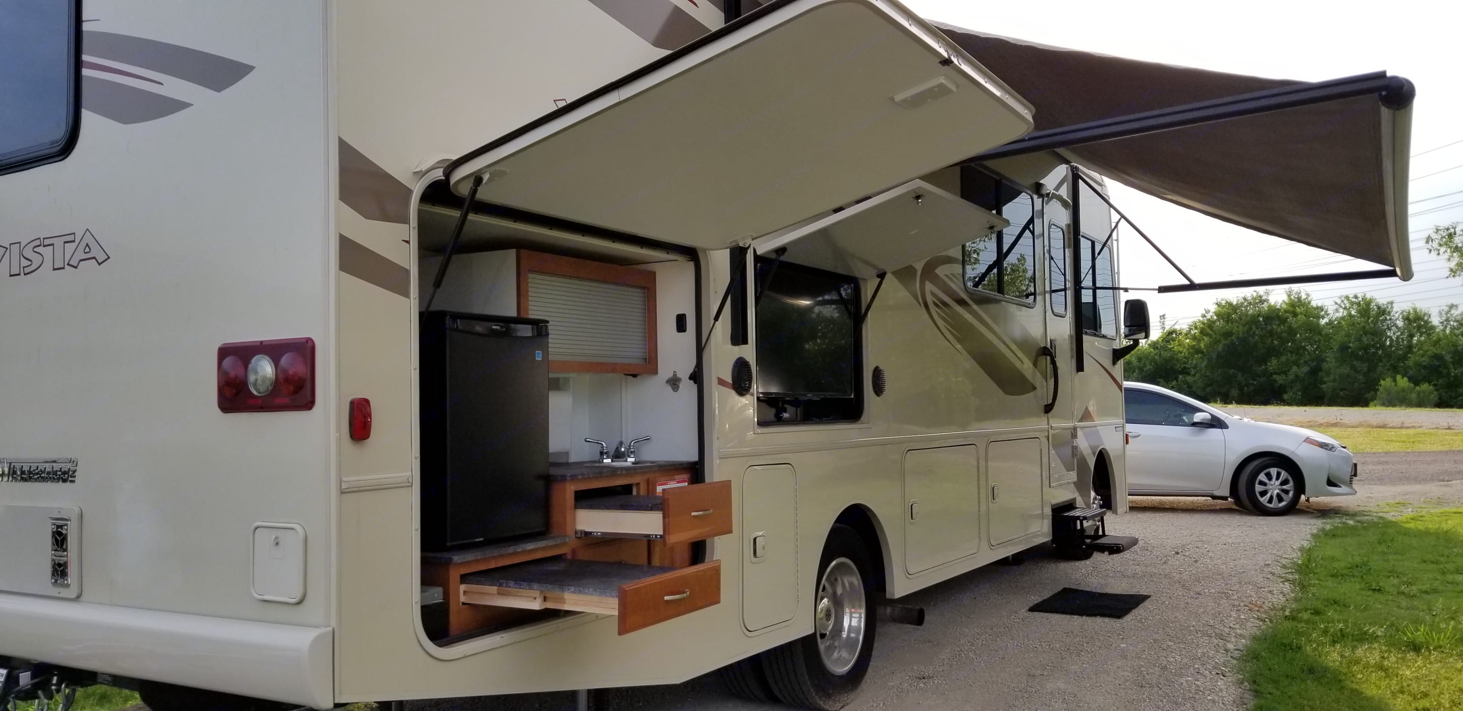 Tailgate package, includes a sink, double prep area and storage compartments. Electric refrigerator (does not cool with LP so mainly for drinks or food while on campgrounds and hooked up to electric) and a gas grill that connects to the LP gas from the RV, so no separate tank is needed.. Winnebago Vista 2017