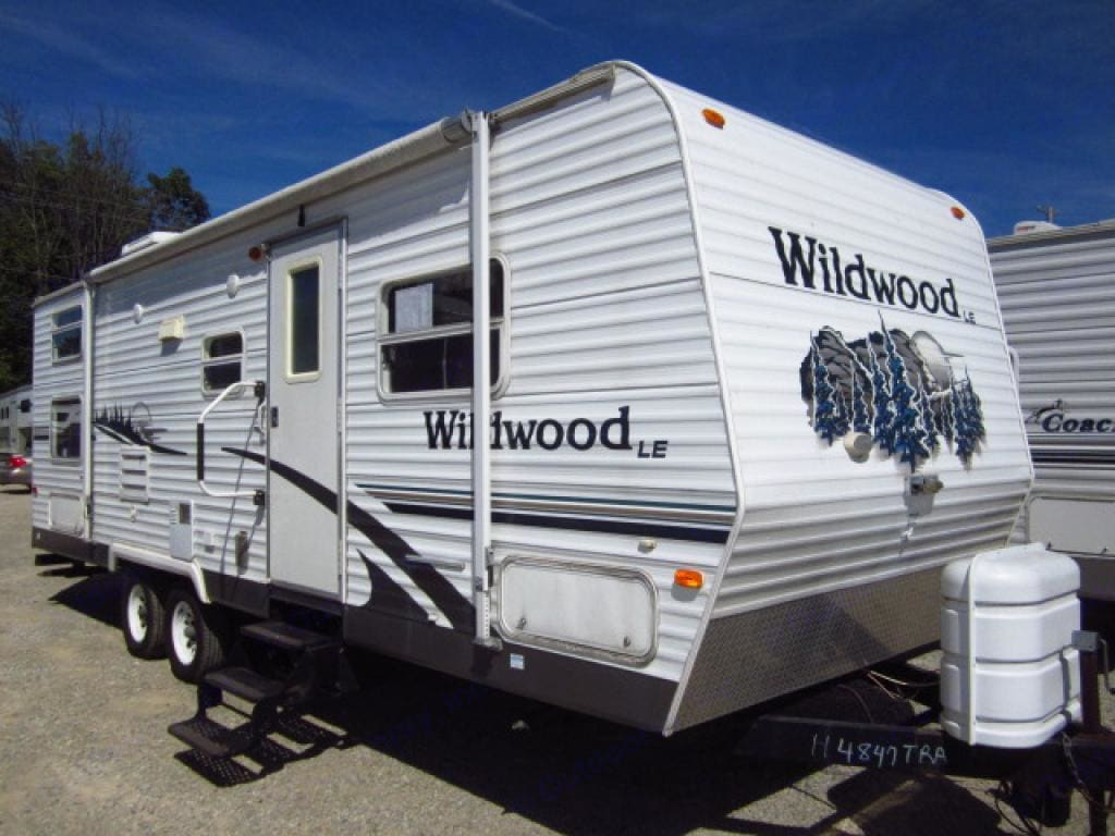 This Wildwood trailer looks fresh and nice with bright and appealing colours of white with blue. There are lots of windows and a patio blind for either sunny or drizzly days. It looks nice in any campground. Almost looks like it was just driven off the dealership lot!. Forest River Wildwood 2006
