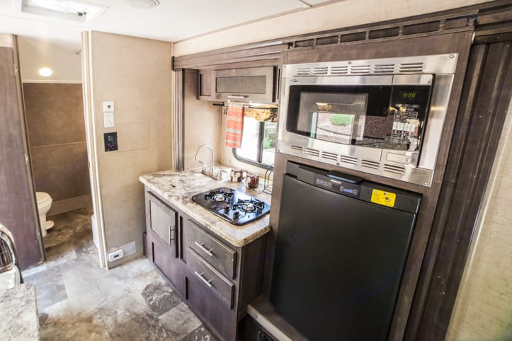 Kitchen including two burner stove, microwave/convection oven, sink, and refrigerator.. Forest River R-Pod 2016