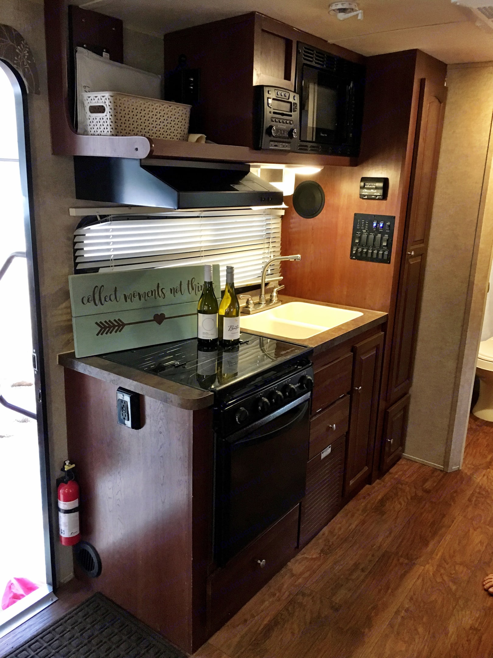 Camper kitchen with oven, 3 burner cook-top, large sink, microwave, tall 4 shelf pantry and (not pictured) fridge and freezer.  Fully stocked with cups, utensils, plates, bowls, cookware and serving ware.. Forest River Rockwood Roo 2015