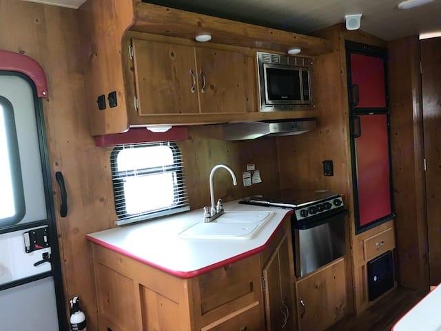 kitchen with stainless steel oven , range, power vent hood, and micro wave . Gulf Stream Cruiser 2018
