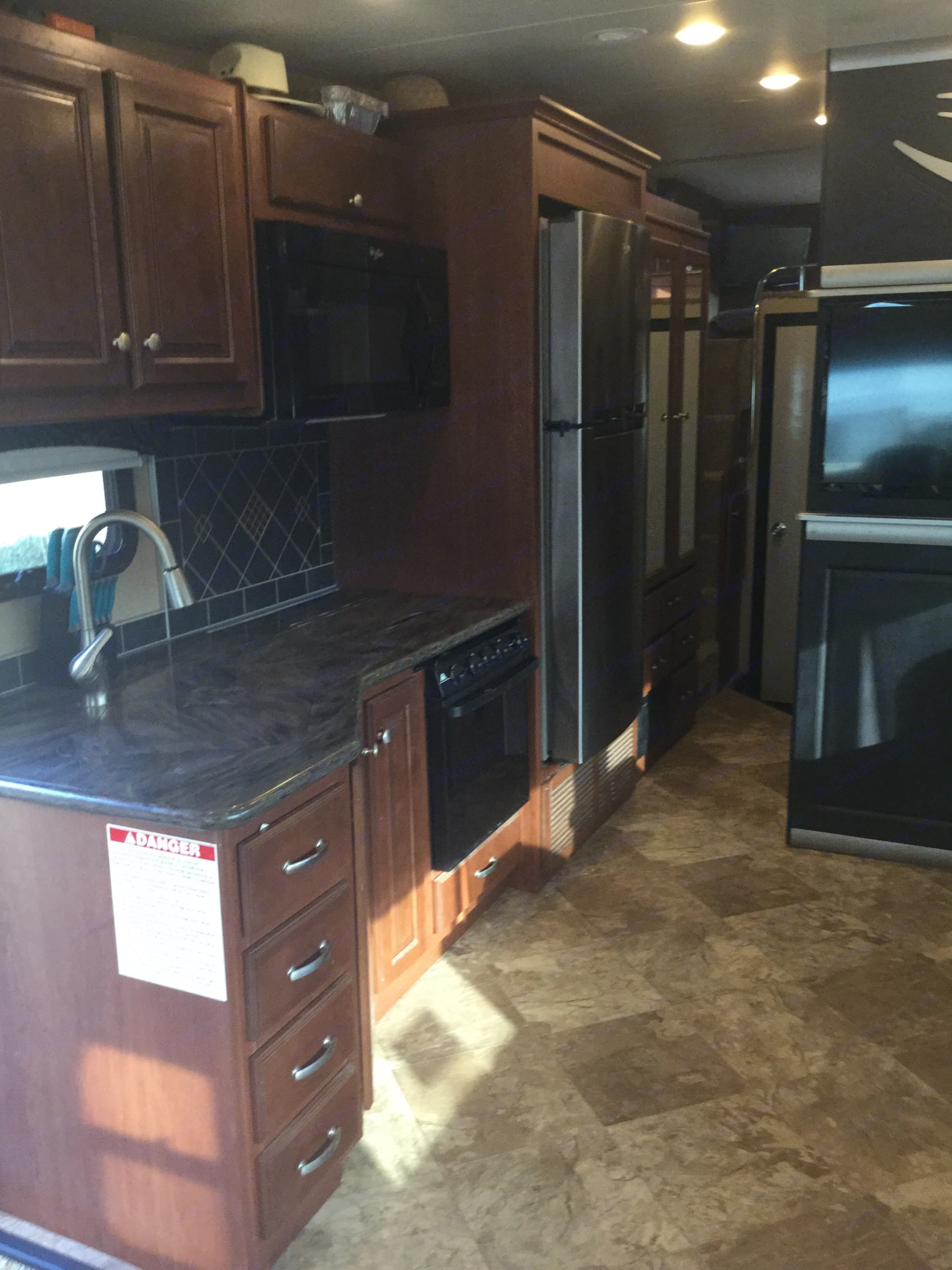Corian countertops with stainless steel refrigerator. Thor Motor Coach Outlaw 2016