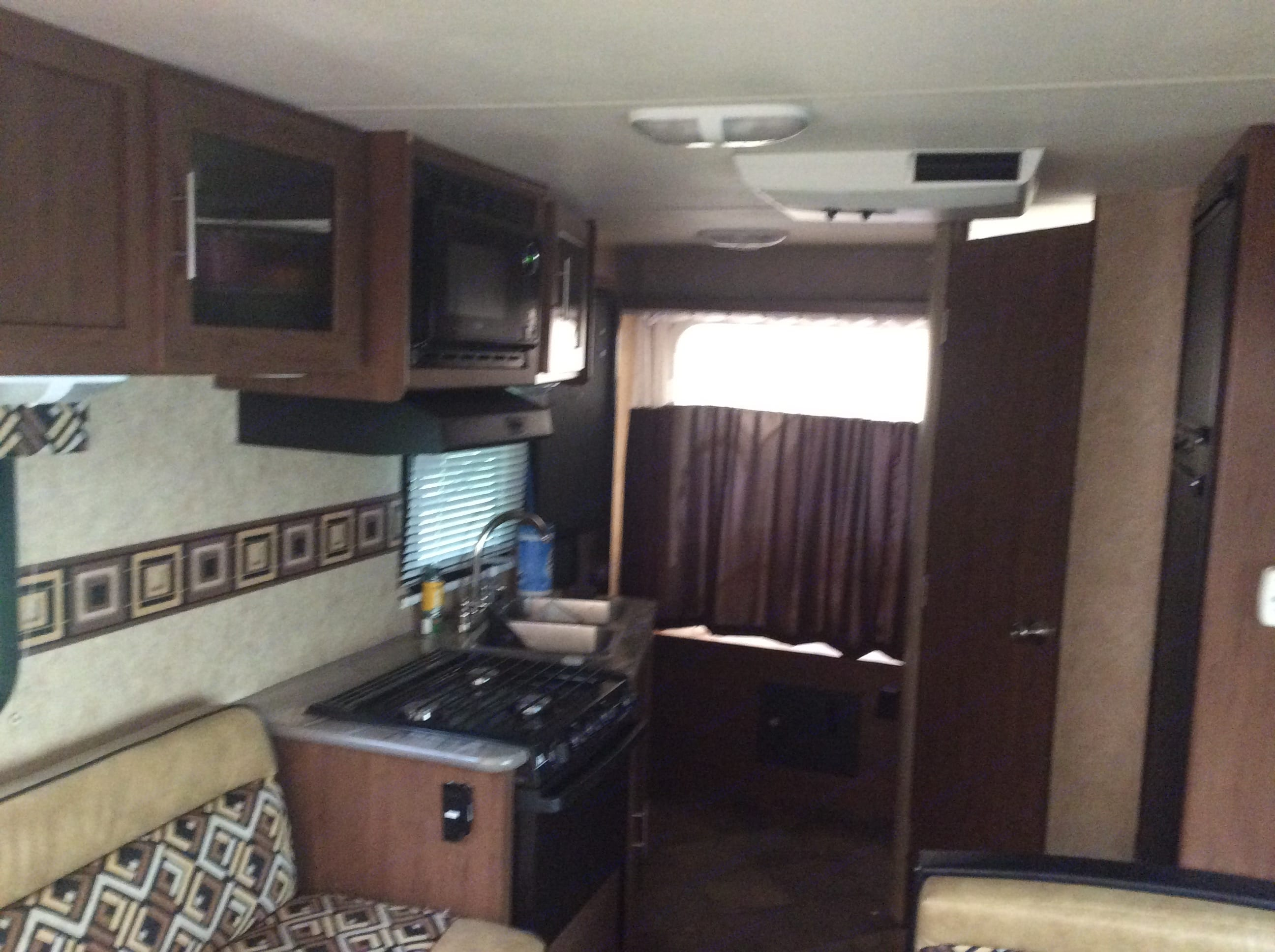 Microwave, Stove, Oven, A/C Unit, Queen size bed behind curtain and door to bathroom.. Dutchmen Aerolite 2013