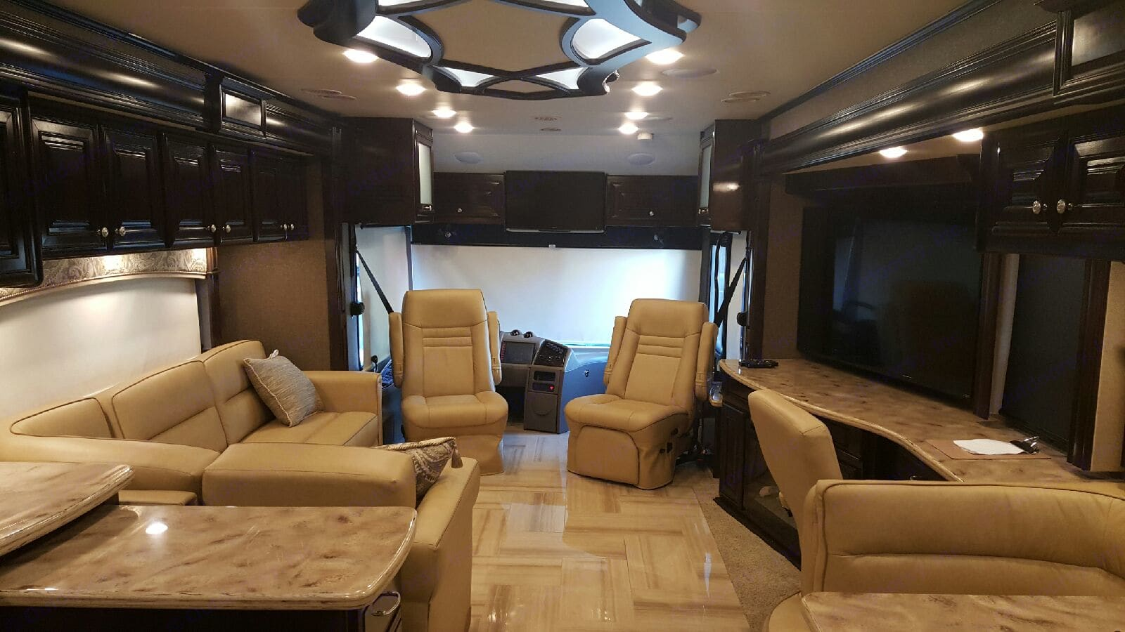 Front lounge area, 32 inch screen TV over driver area, 60 inch screen TV in lounge area with fireplace, work station desk area.. Thor Motor Coach Tuscany 2016