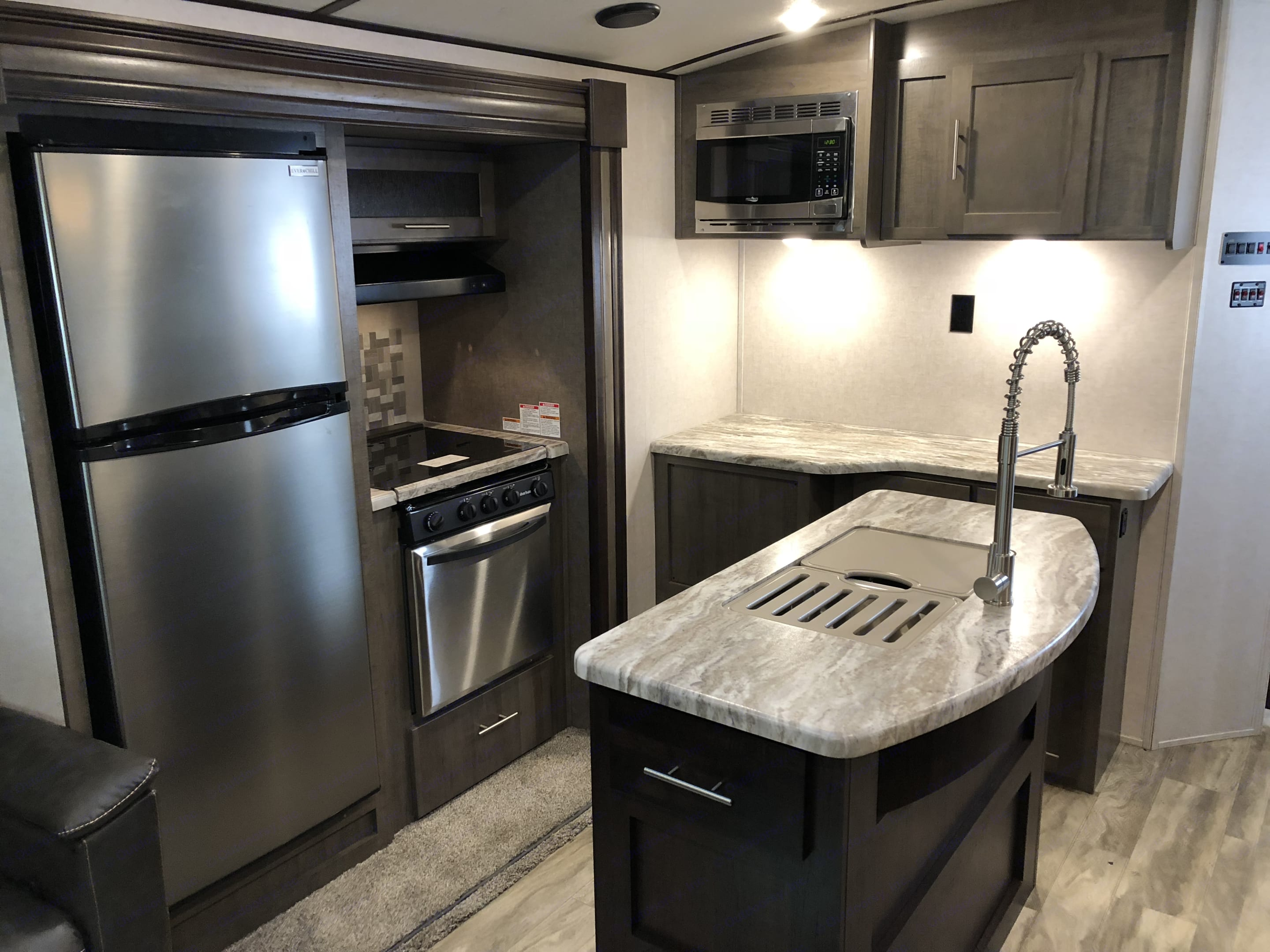 Spacious kitchen with island and lists of storage. Full size refrigerator and a 3 burner stove top oven. . Forest River Surveyor 2019