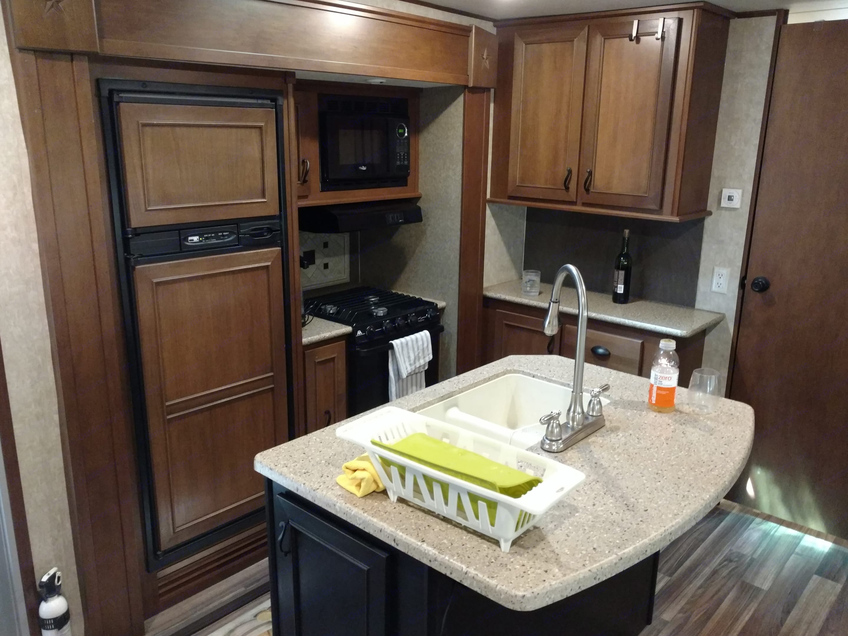 Opposite slide out showing island, refrigerator and stove-top/oven. Kitchen is quite pleasant for two people to prepare food.. Open Range Light 2016