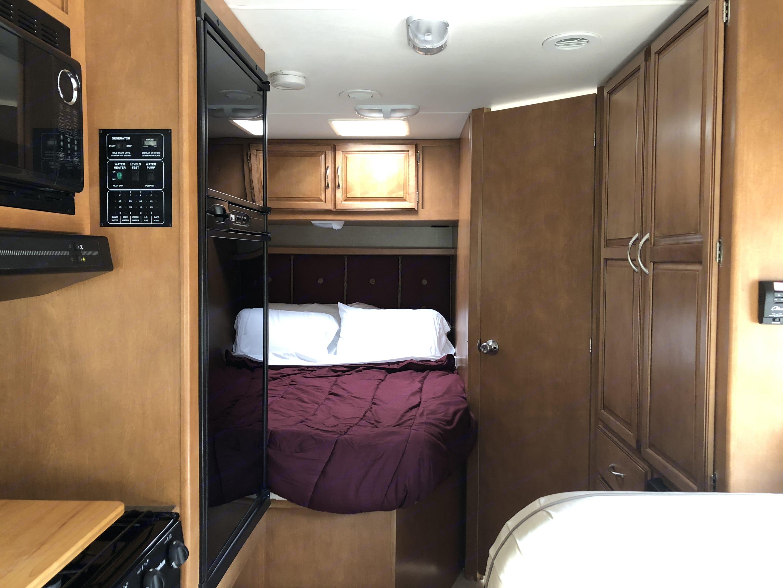 Back view of interior including back bed, closet and bathroom doors. Winnebago Minnie Winnie 22R 2016