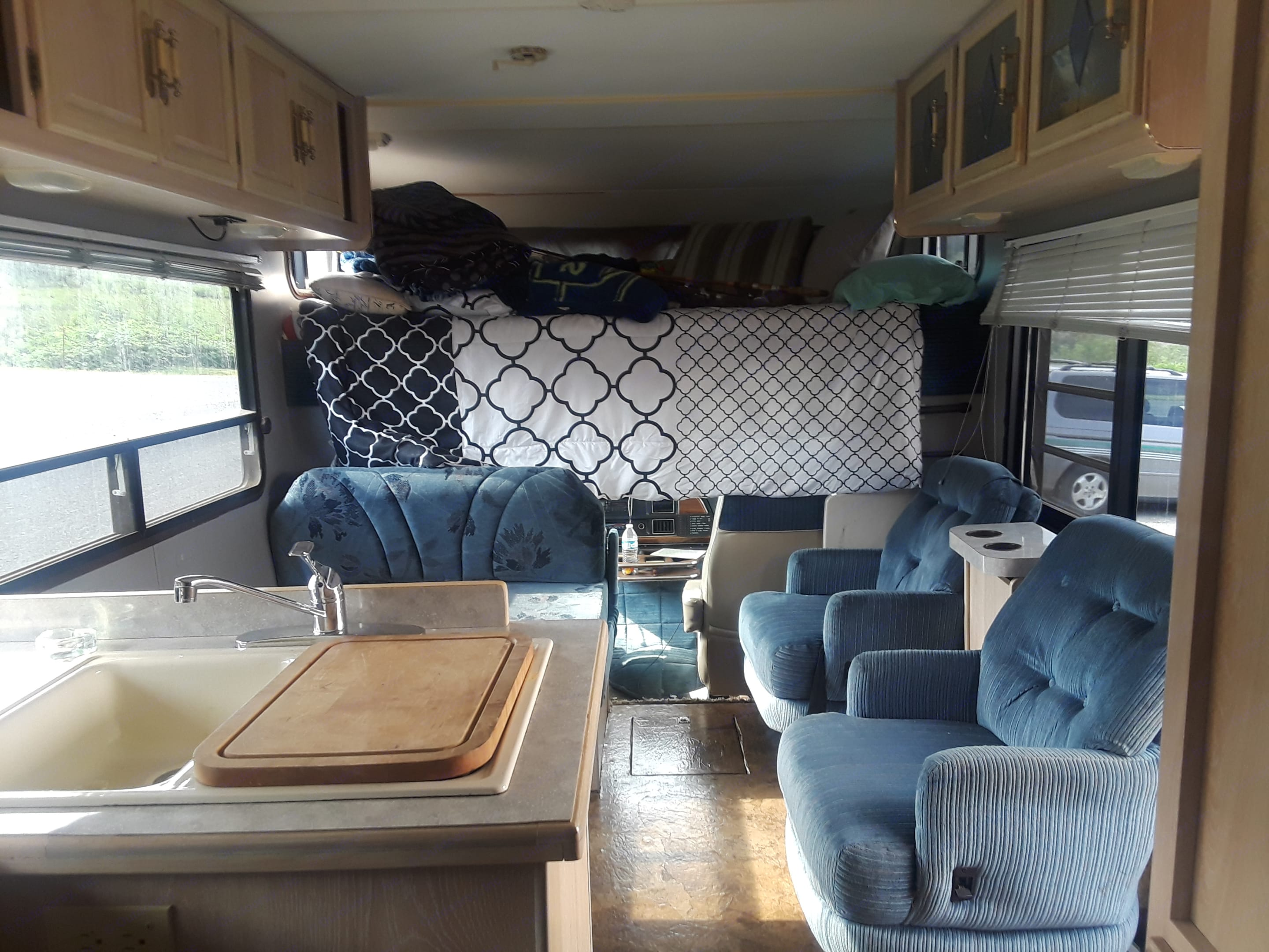 Upper bed and dining table from bathroom area. Coachmen Leprechaun 1991