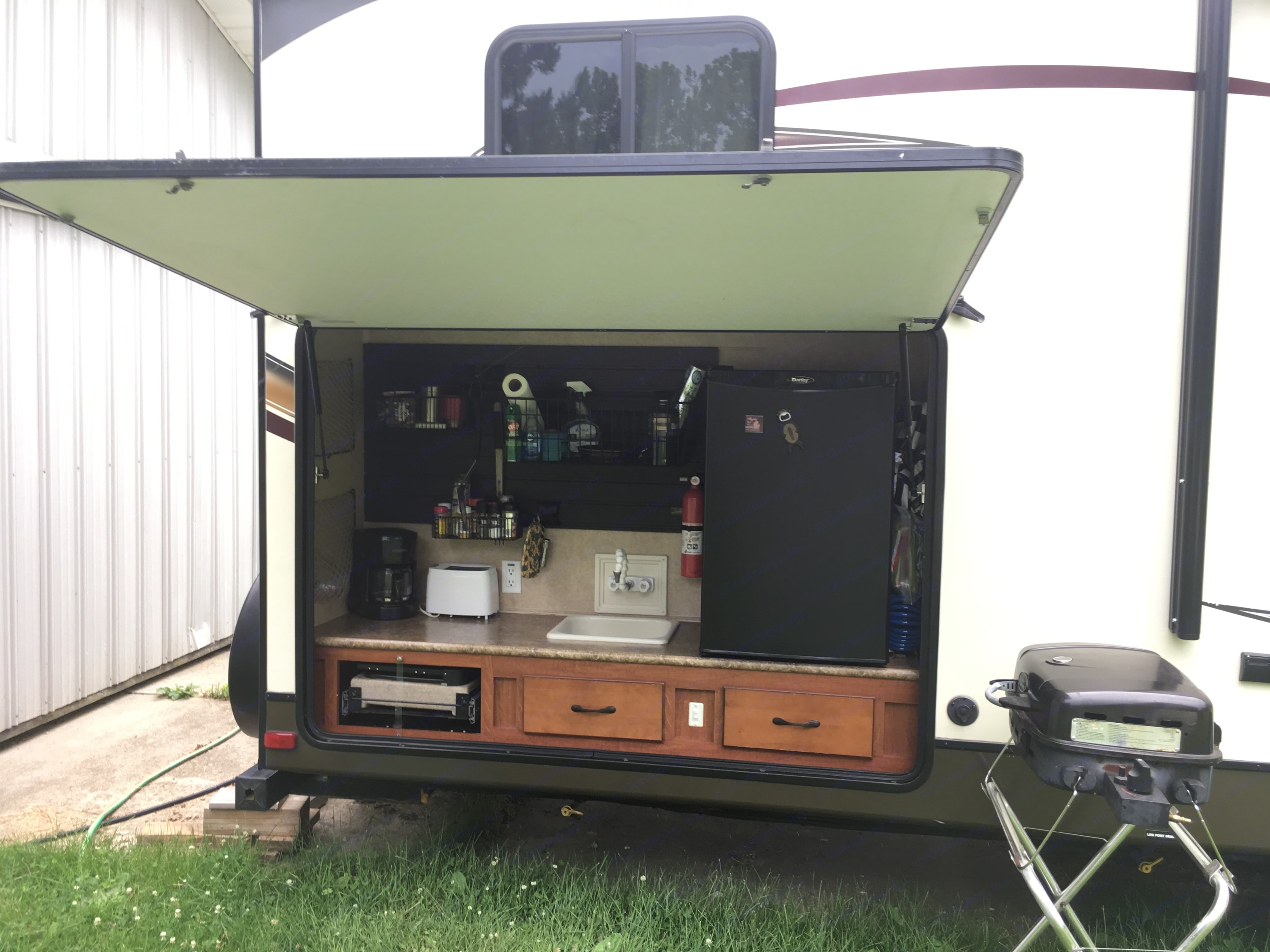 The full size outdoor kitchen has a fridge, sink, cook-top stove, coffeepot, toaster and optional BBQ-grill. . Forest River Surveyor select 10th anniversary edition 2012