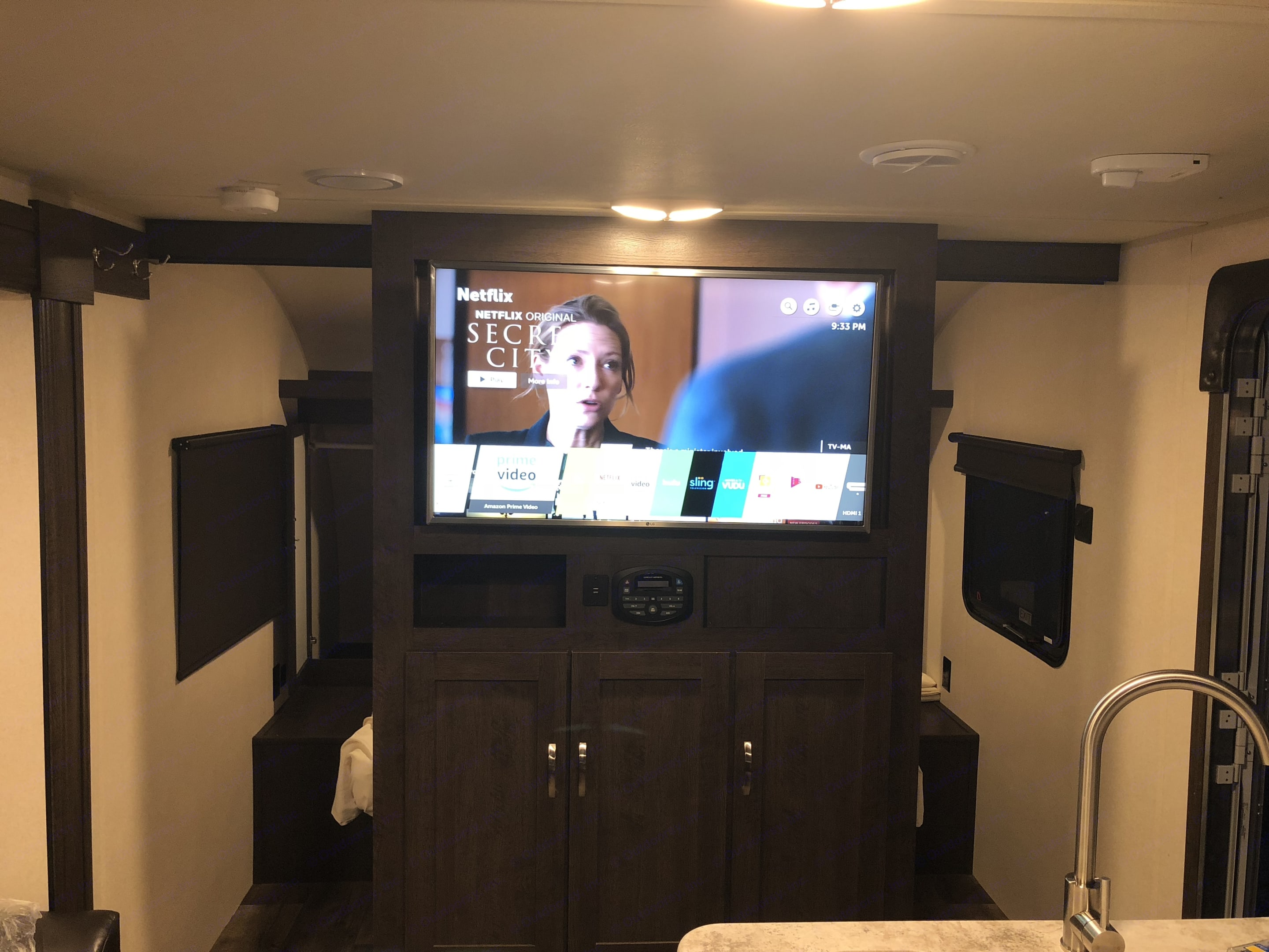 Entertainment center with storage underneath. Queen bed with solid slide out doors instead of curtains is behind it!. Forest River Salem Cruise Lite 2018