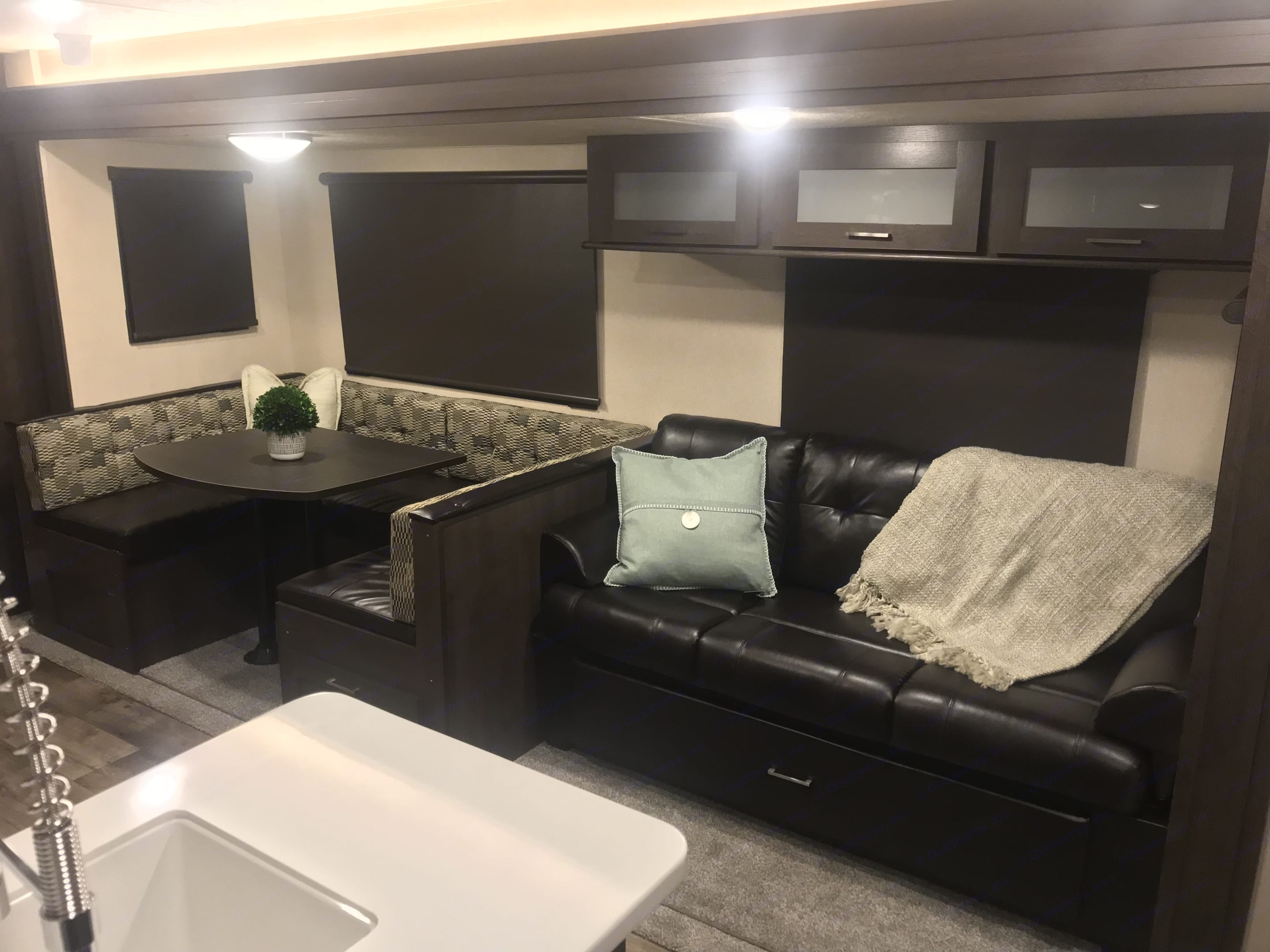The couch has storage above it in the cabinets and below it. There is also storage under the dining area.. Forest River Wildwood 32BHDS 2018
