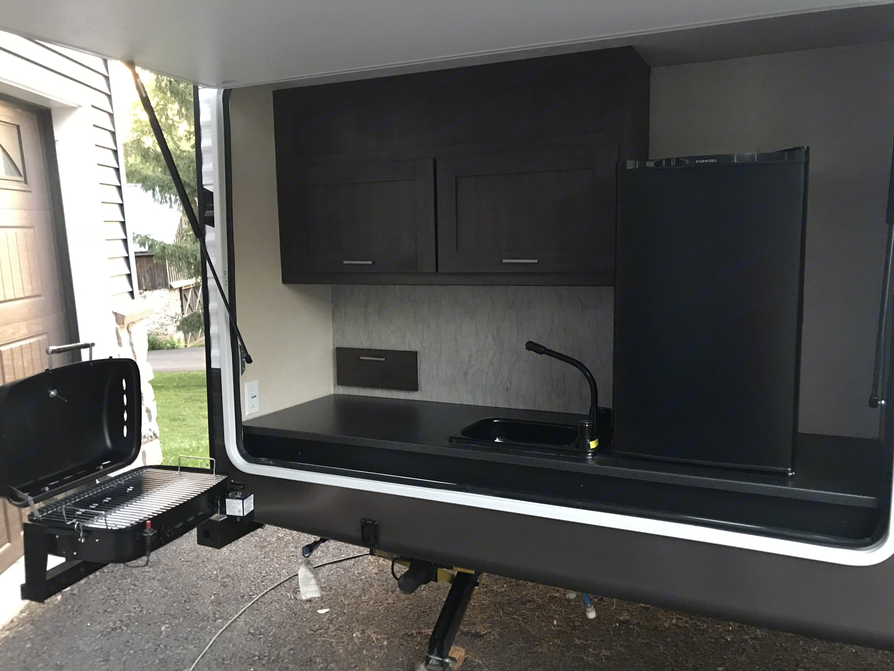 The outdoor kitchen has a mini fridge, a sink, plenty of storage, and a grill that swings around that is attached to the bumper.. Forest River Wildwood 32BHDS 2018