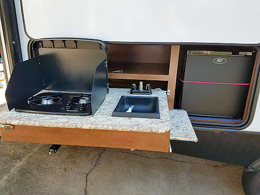 Outside Kitchen includes 2 burner gas stove (propane included), mini-fridge and sink.  Both sides of the counter extend for extra prep space.. Keystone Passport 2017