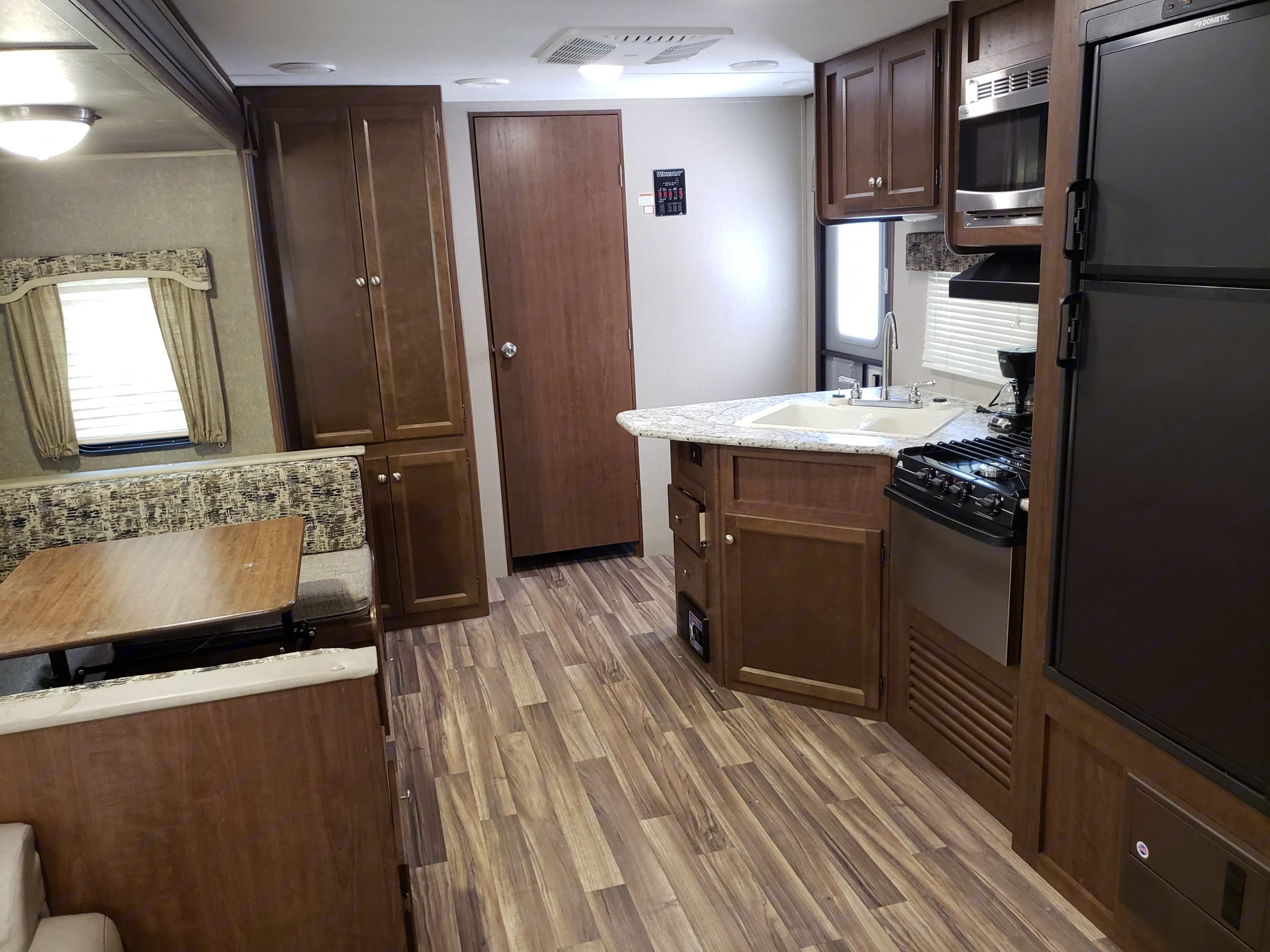 """Spacious kitchen and dining area including: U-shaped bench with table, Sink, Gas Stovetop/Oven, Microwave, Fridge/Freezer, Closet/Cabinet Space, and Door leading to the """"Master"""" bedroom.. Keystone Hideout 2017"""