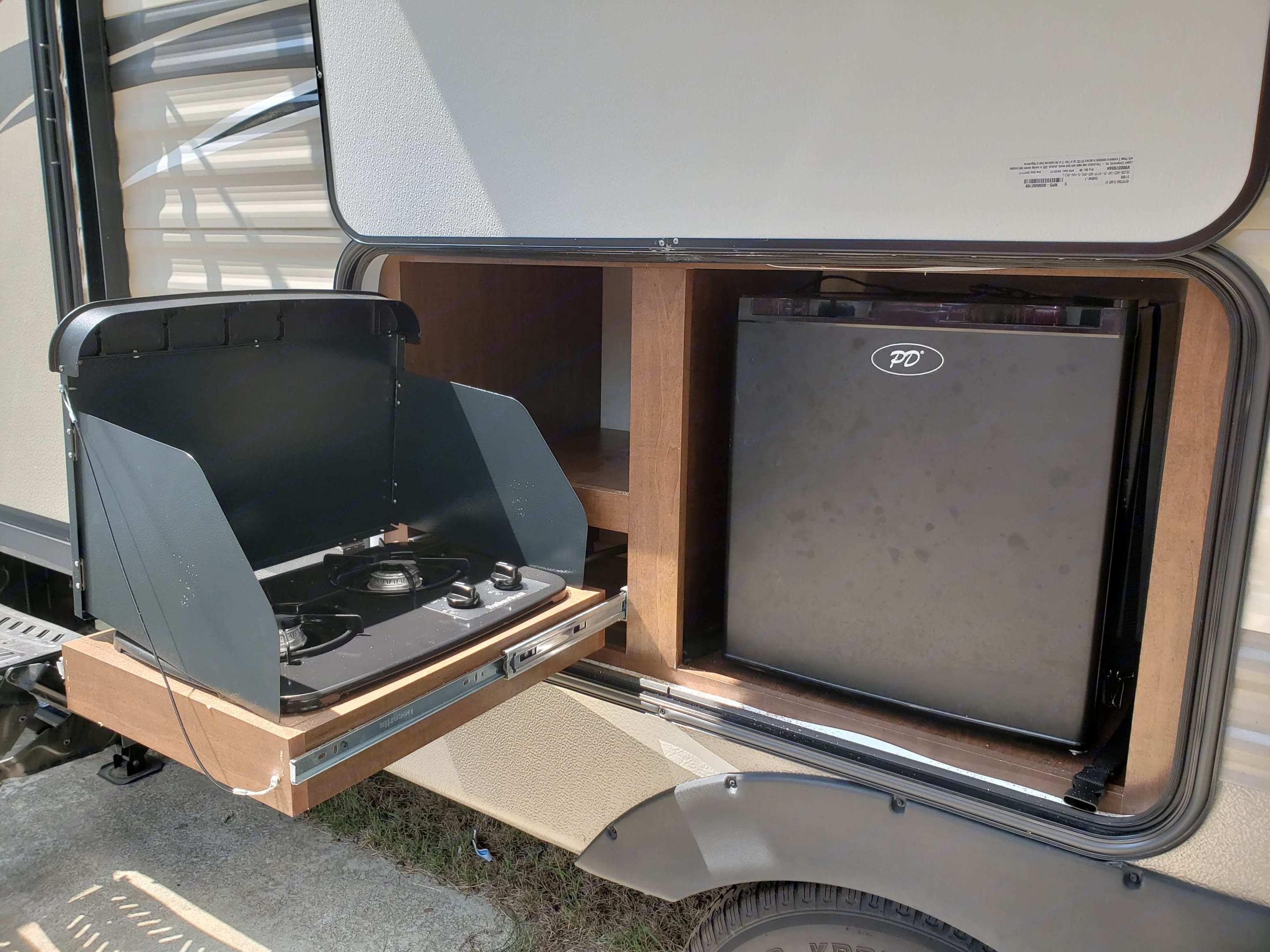 Outdoor kitchen with two gas burner stove and mini fridge.. Keystone Hideout 2017