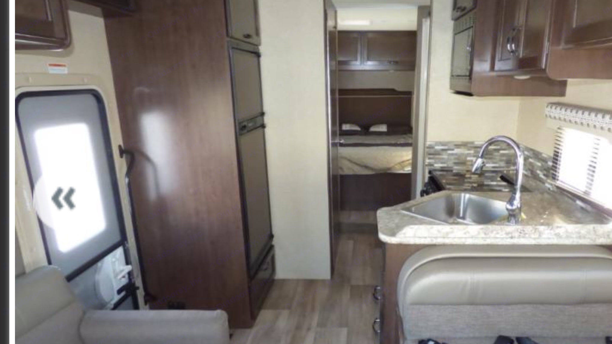 Kitchen, and rear bedroom with walk-around queen bed.. Thor Motor Coach Four Winds 2018