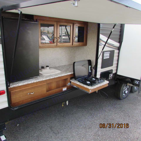 Outdoor kitchen with sink, mini fridge, storage and a propane stove. Prime Time Avenger 2016