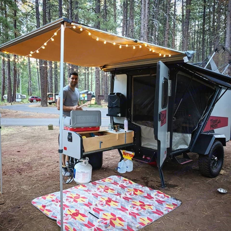 Both hatch doors open with screens attached. Kitchen drawer pulled out with cooking stove, and cubbies for food and cooking accessories. The 5 gallon drinking water jug attached right above the cutting board. Underneath the drawer we usually keep our fuel and cooler. The cooler is available by request and keeps ice for days at a time as long as the lid is shut tightly. . TAXA Outdoors Tigermoth Camper 2018