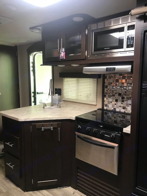 Kitchen with deep sink, microwave, gas range and stove Fridge/freezer . Forest River Cherokee Grey Wolf 2017