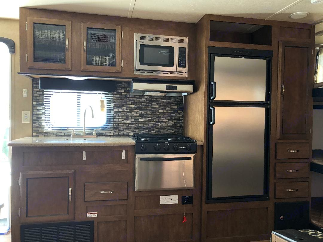 Kitchen includes microwave, stove, and oven.  Kitchen includes pots and pans along with cooking utensils. Forest River Salem 2015