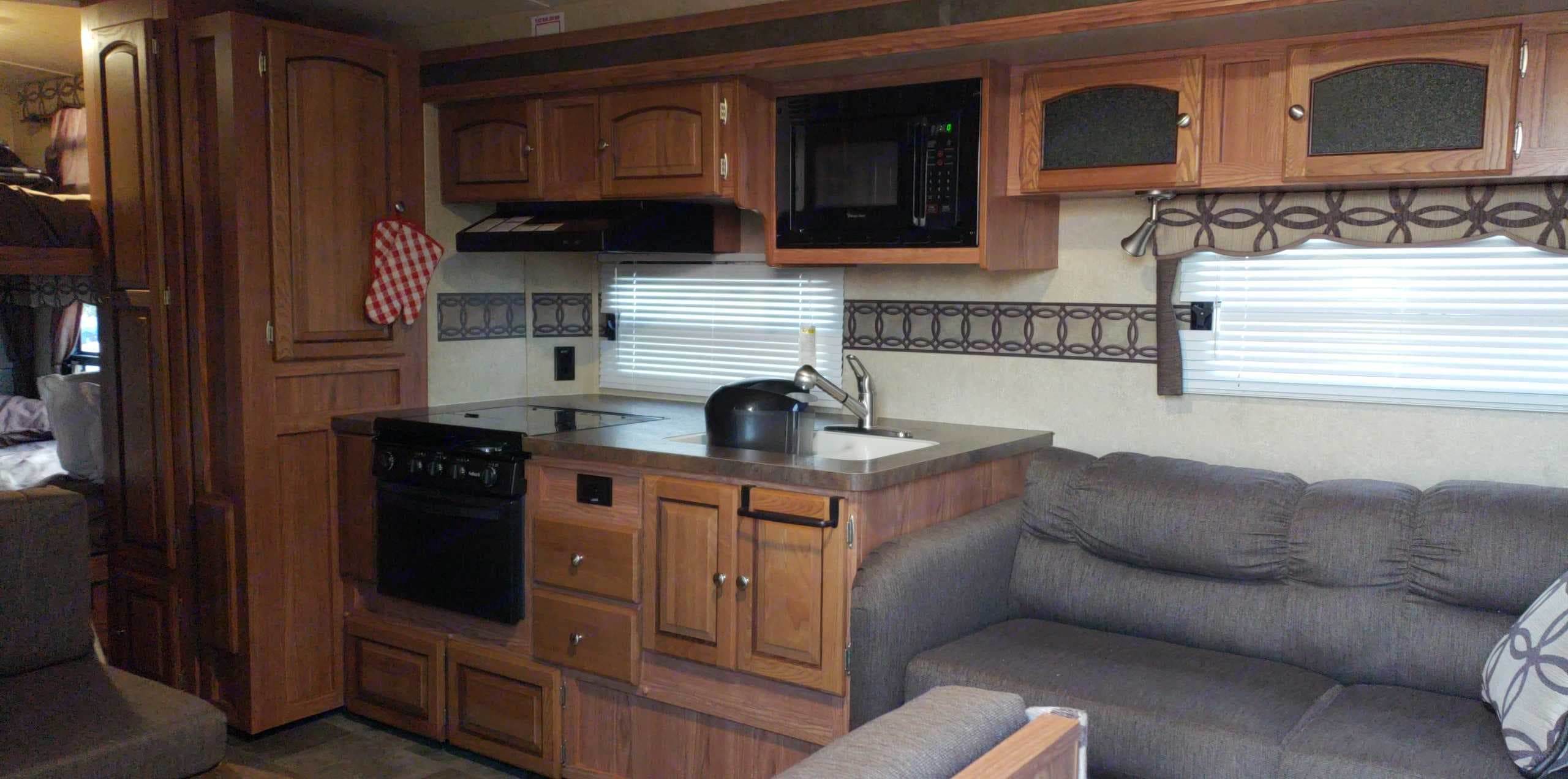 Kitchen with gas oven and cooktop, microwave, Keurig, utensils, cookware, drinkware, plates and bowls. Flagstaff Super Lite 2016