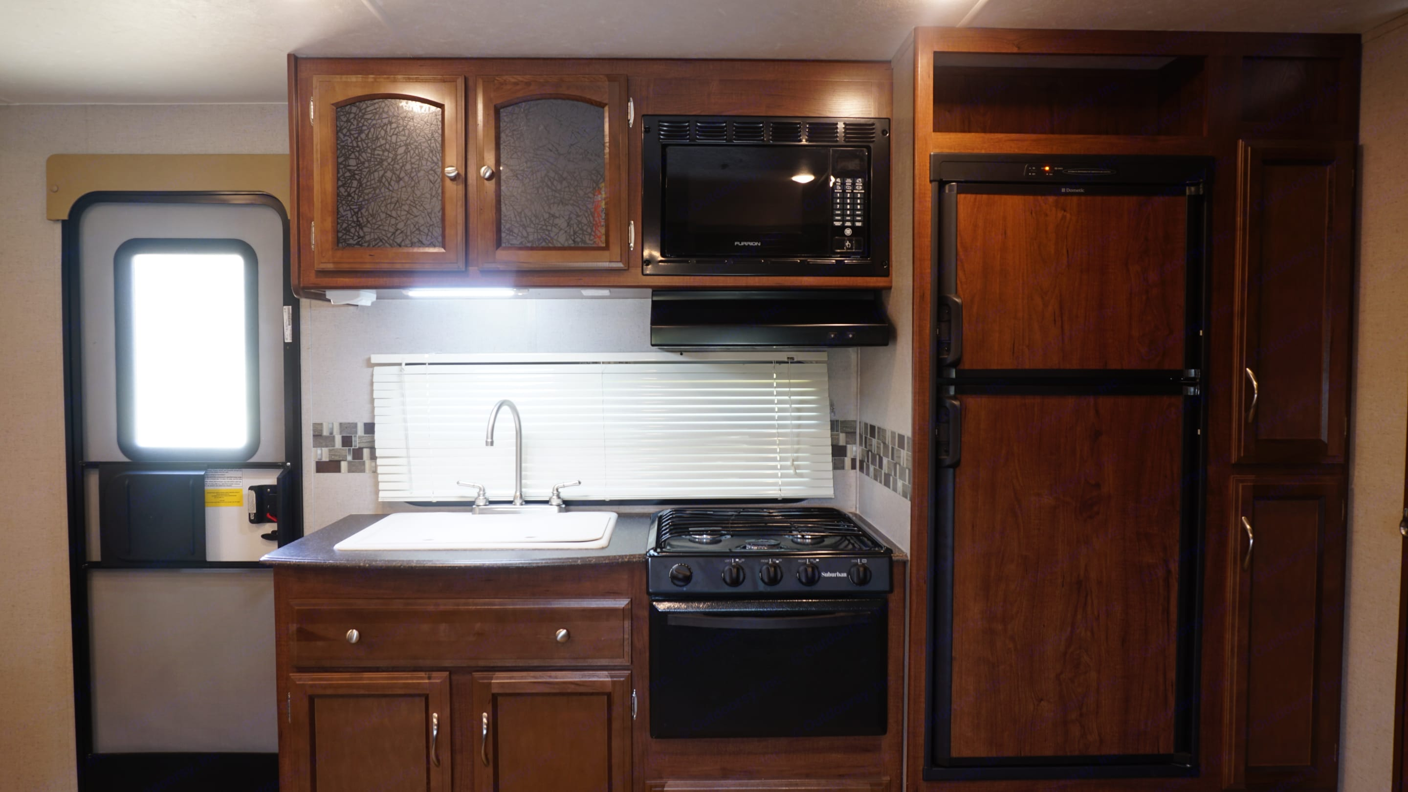 Kitchen with Fridge/Freezer, Stove Top, Oven, Microwave, Sink, and Storage. Coachmen Freedom Express 2016