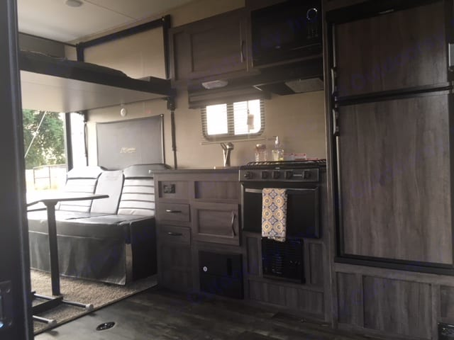 Roomy kitchen and living area, the two benches fold down into two full size beds.  Linens included.. Pacific Coachworks Rage'N 2019